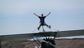 Michaela taking part in our June 2018 Wing Walk with her legs and arms raised in celebration.