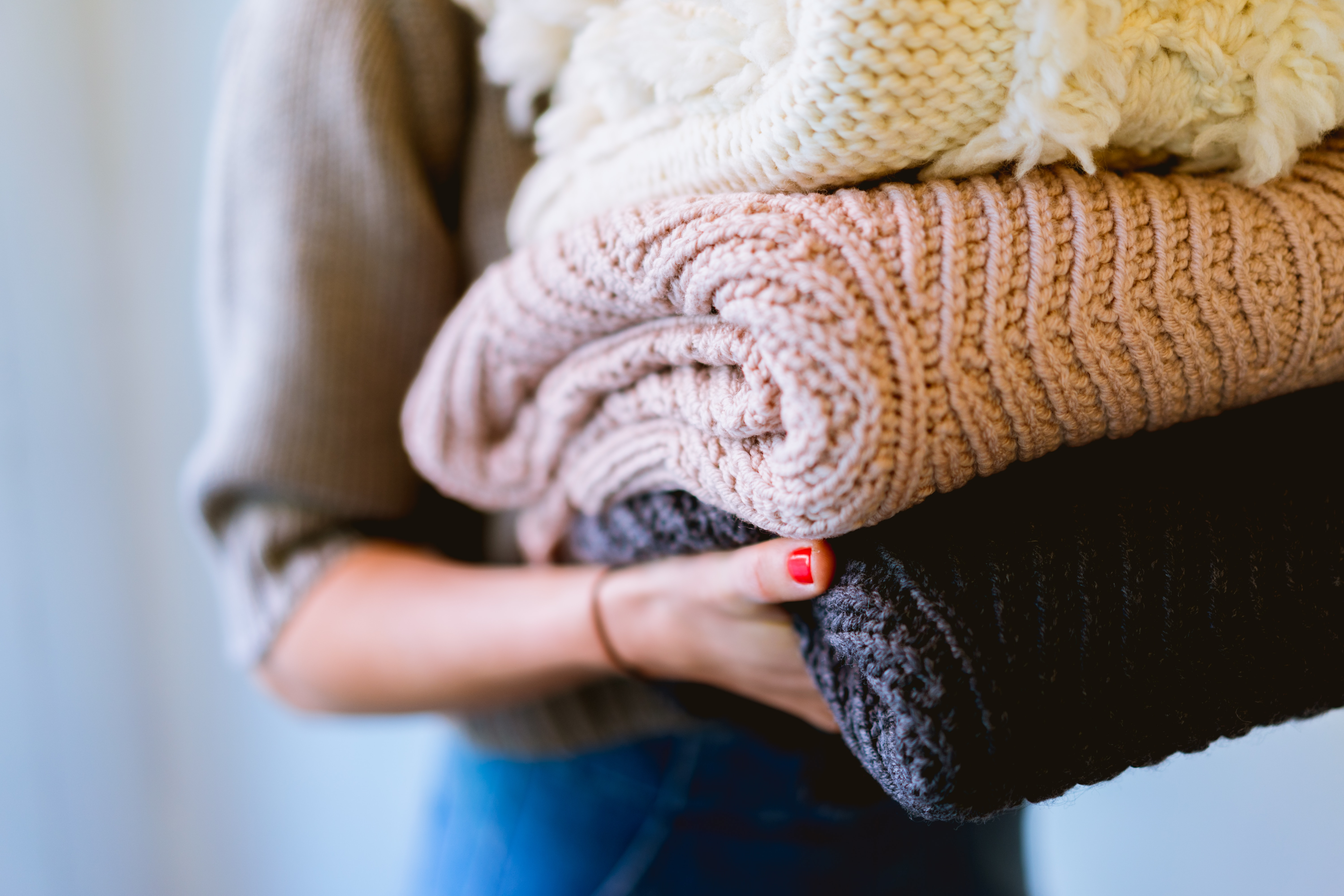 A woman carrying a pile of folded jumpers