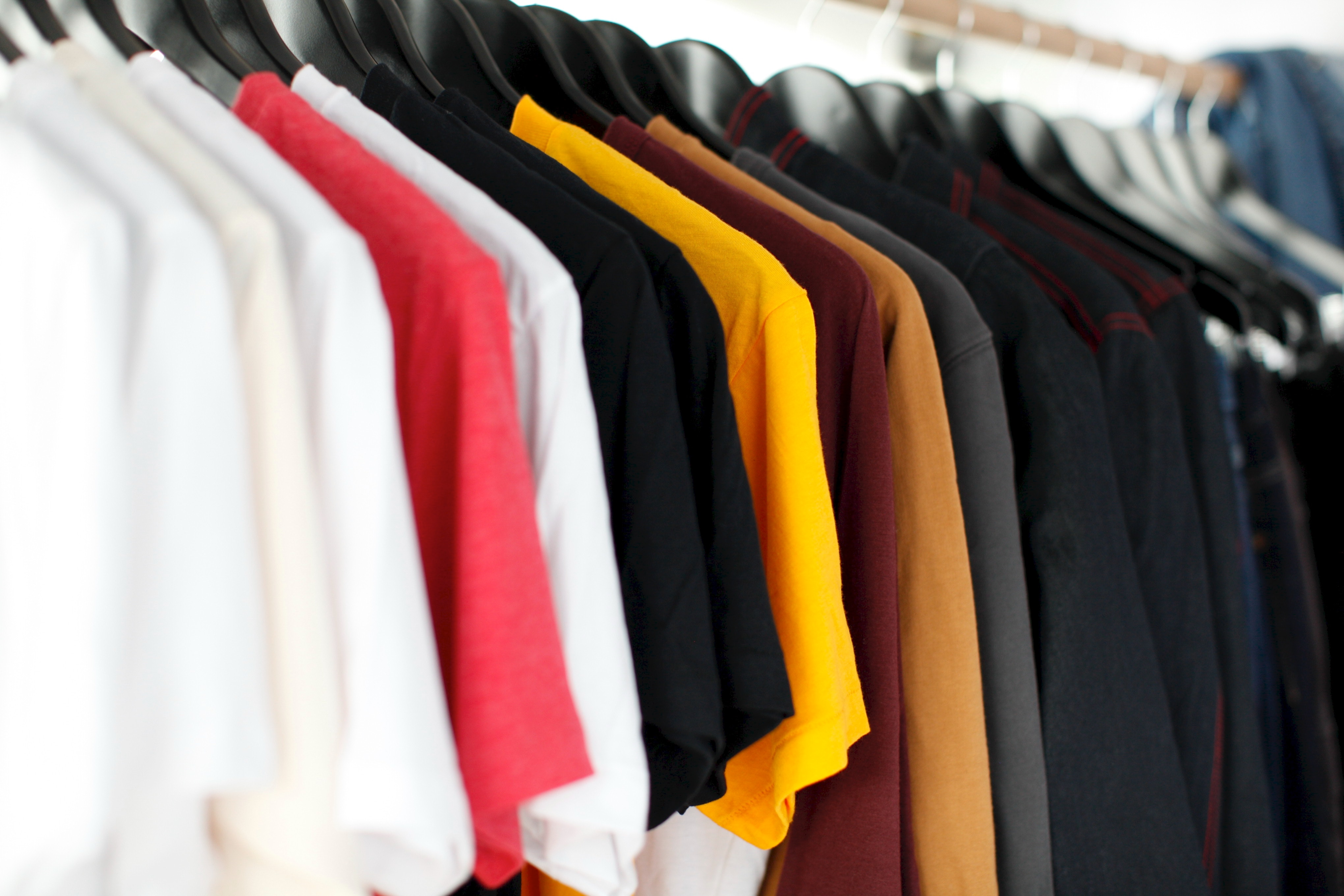 A row of various colour tshirts hanging on a clothes rail